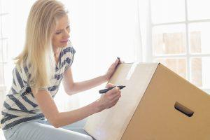 girl writing on box